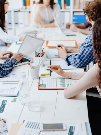 Mensen uit het bedrijfsleven ontmoeten elkaar op kantoor, ze bespreken financiële strategieën en controleren financiële rapporten