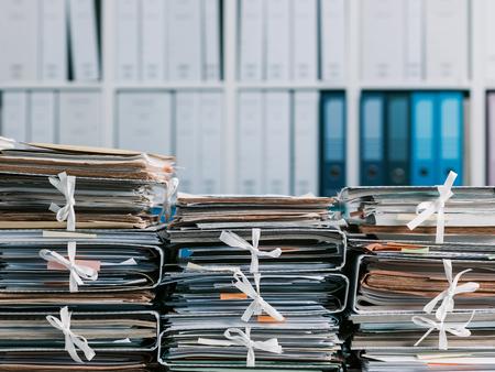 Pilas de archivos y documentos en la oficina y estanterías en el fondo: concepto de gestión y almacenamiento