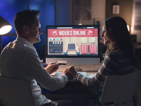 Young loving couple watching series and movies online together, they are holding hands and looking at each other Stock Photo