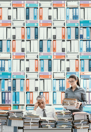 Betonter Geschäftsmann, der am Schreibtisch arbeitet und mit Arbeit überladen ist, der Schreibtisch wird mit Schreibarbeit bedeckt, seine Sekretärin holt mehr Akten Standard-Bild