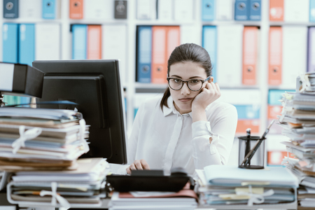 Young bored office worker sitting at desk and working, she is overloaded with paperwork