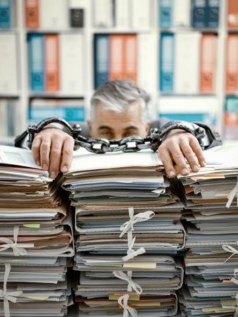 Überarbeiteter gestresster Geschäftsmann angekettet an den Arbeitsplatz, er ist überlastet mit Arbeit und liegt auf Papierstapeln auf seinem Schreibtisch