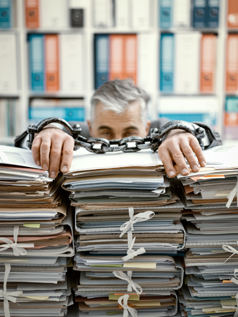 Overworked stressed businessman chained to the workplace, he is overloaded with work and lying on piles of paperwork on his desk