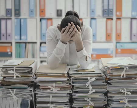Frustrated you office worker leaning on piles of paperwork, she is overloaded with work and stressed Stock Photo