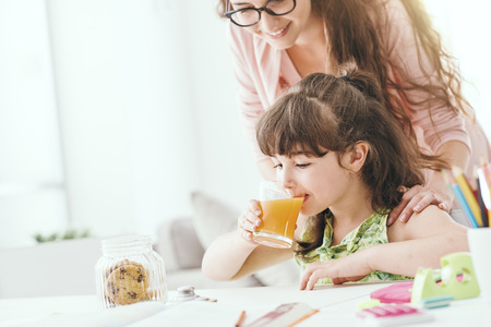 Cute preschool girl having a snack with her mother, she is drinking some orange juice, family and healthy lifestyle concept