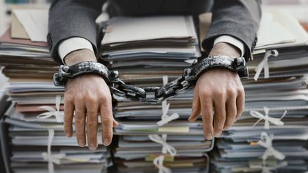Uomo d'affari stressato oberato di lavoro incatenato al posto di lavoro, è sovraccarico di lavoro e giace su pile di scartoffie sulla sua scrivania