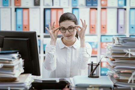 Confident secretary sitting at office desk and adjusting her glasses