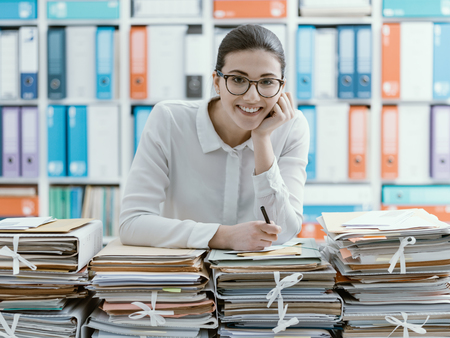 Smiling young office worker leaning on piles of paperwork