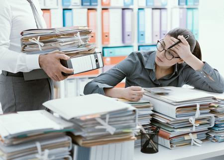 オフィスの若いストレスを受けた秘書は、ファイルでいっぱいの仕事と机に圧倒され、彼女の上司は彼女に多くの書類をもたらしています 写真素材 - 96095020