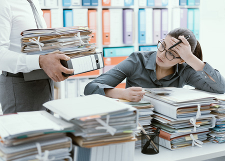 Young stressed secretary in the office overwhelmed by work and desk full of files, her boss is bringing more paperwork to her 스톡 콘텐츠