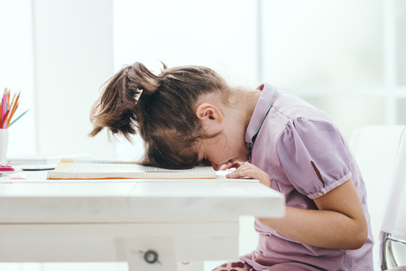 Lazy student girl at home, she is resting with her face down on the school book, education and childhood concept Stockfoto