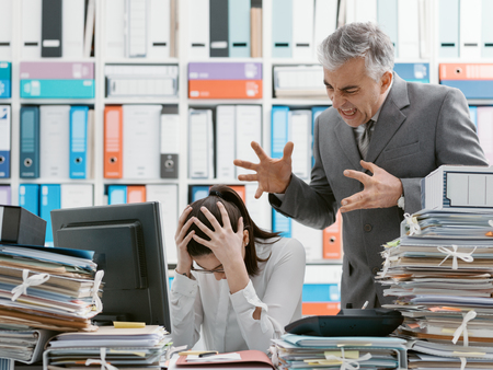 Angry boss yelling at his young employee, she is stressed and feeling frustrated: hostile boss and mobbing concept