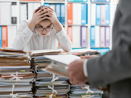 Exhausted young secretary overloaded with work, her boss is bringing more paperwork to her Stock Photo