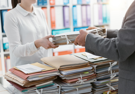 Boss handing paperwork to his employee, she is overwhelmed by work