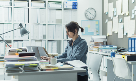 Efficient female office clerk sitting at desk in the office and working