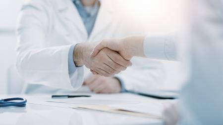 医者と患者がオフィスで握手をし、彼らは机に座って、手をクローズアップ 写真素材