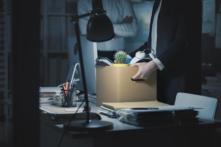 Chef feuert einen jungen Angestellten im Büro, sie packt ihre Sachen und hält eine Pappschachtel in der Hand
