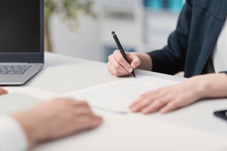 Die Geschäftsleute, die im Büro sich treffen, eine Frau unterzeichnet einen Vertrag: Vereinbarungs- und Einstellungskonzept