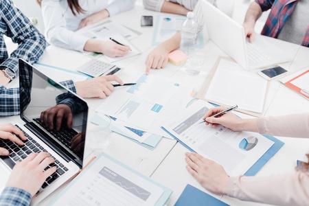 Reunión del equipo de negocios en la oficina y discutiendo estrategias financieras, están revisando informes y documentos, personas irreconocibles