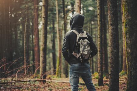 Jonge man met een kap wandelen in het bos, vrijheid en natuur concept