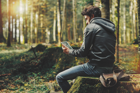 Young handsome man sitting in the woods and using a digital touch screen tablet, wi-fi connection and freedom concept Stockfoto