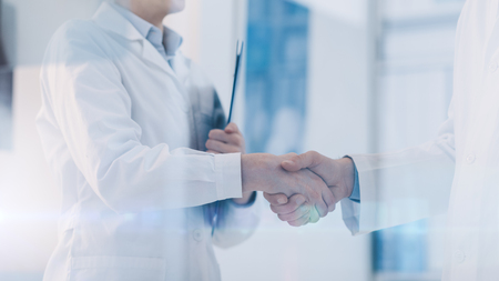 Young female doctor shaking hands with her colleague, healthcare and cooperation concept