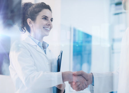 Young female practitioner shaking hands with a doctor, career and healthcare professionals concept