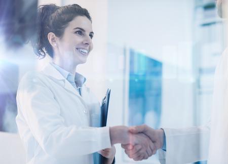 Jonge vrouwelijke arts handen schudden met een arts, carrière en gezondheidszorg professionals concept