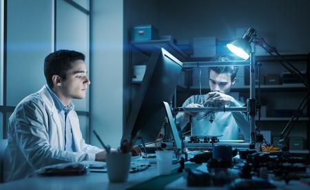 Engineeringteam werkt 's nachts in het lab, een student werkt met een computer en de andere past de componenten van een 3D-printer aan