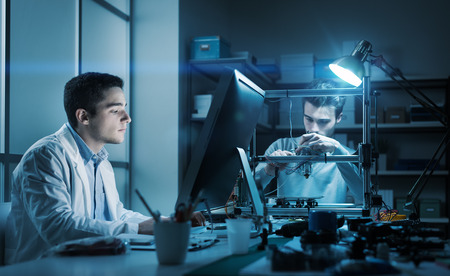Zespół inżynierów pracujący w laboratorium w nocy, student pracuje z komputerem, a drugi dostosowuje podzespoły drukarki 3D Zdjęcie Seryjne