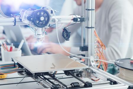 Impresora 3D innovadora en el laboratorio, un estudiante está trabajando con una computadora portátil en segundo plano