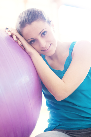 Attractive smiling woman exercising at gym with fitness ball, sitting on the floor.