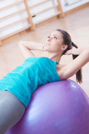 Attractive young woman working out with fitness ball in the gym, pilates exercise. Stock Photo - 97989942