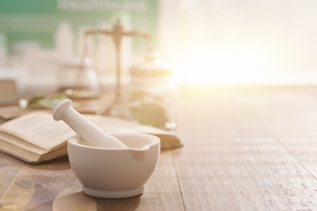 Mortar and pestle with pharmaceutical preparations's book and herbs on a wooden pharmacist table, traditional medicine and pharmacy concept
