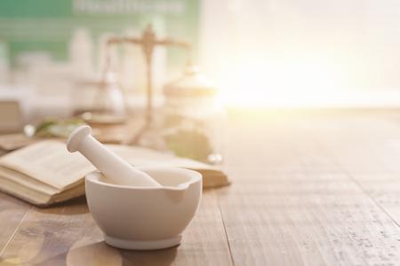 Mörser und Stampfe mit dem Buch und den Kräutern der pharmazeutischen Präparate auf einem hölzernen Apothekertabellen-, -traditionsmedizin- und -apothekenkonzept
