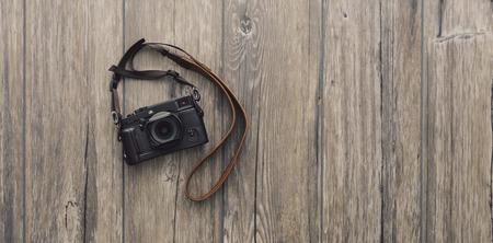 Professional digital camera with strap on a vintage wooden desktop