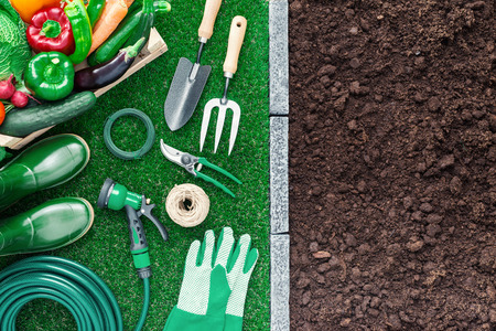 Gardening tools on the grass and fertile humus soil; gardening and agriculture concept, top view