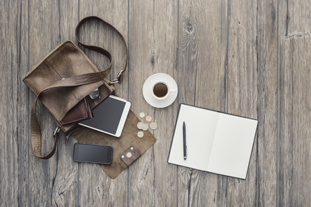 Hipster bag on a desktop with tablet, smartphone and a blank notebook, top view Stock Photo
