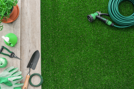 Gardening tools on a wooden table and lush grass, hobby and garden manteinance concept Standard-Bild