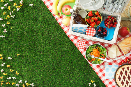 Summertime picnic setting on the grass with open picnic basket, fruit, salad and cherry pie