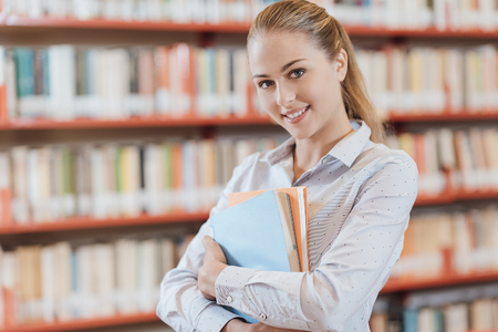 Confident student girl posing at the library, she is smiling and holding books, bookshelves on the background Foto de archivo - 98892963