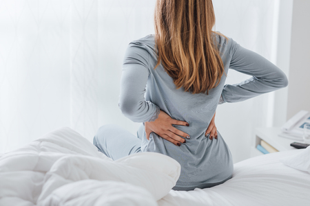 Young woman with back ache, she is sitting on the bed and touching her back
