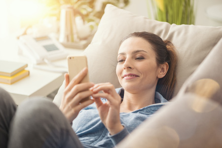 Relaxed smiling woman on the couch at home, she is using a smartphone and texting Archivio Fotografico