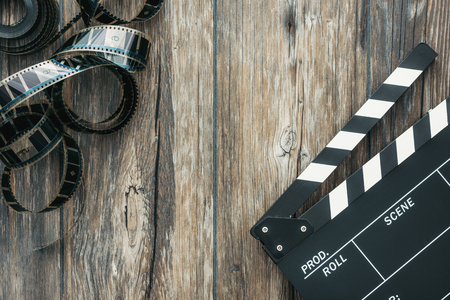 Filmstrip and clapper board on a rough wooden surface, cinema and videomaking concept Stock Photo