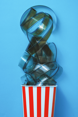 Filmstrip in a popcorn striped box on blue background, cinema and entertainment concept