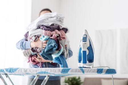 主婦は、アイロン台に洗濯物の巨大な山をもたらす、退屈な家事のコンセプト 写真素材