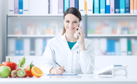Smiling nutritionist having a phone call and scheduling appointments, healthy eating and healthcare concept Stock Photo