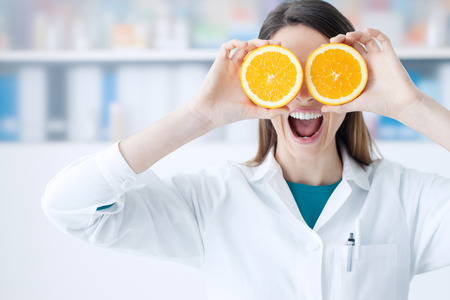 Funny female dietist holding oranges over her eyes, diet and nutrition concept