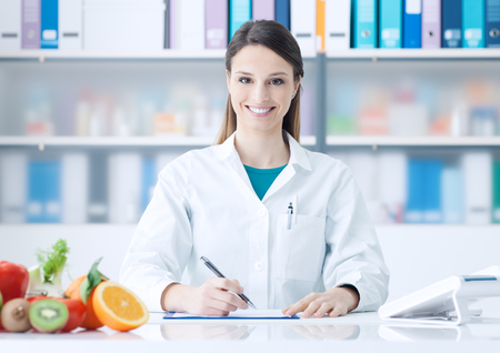 Smiling female nutritionist working at office desk with healthy fruit and vegetables on foreground
