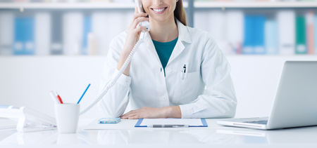 Smiling female doctor working at office desk and answering phone calls, healthcare and consulting concept Foto de archivo
